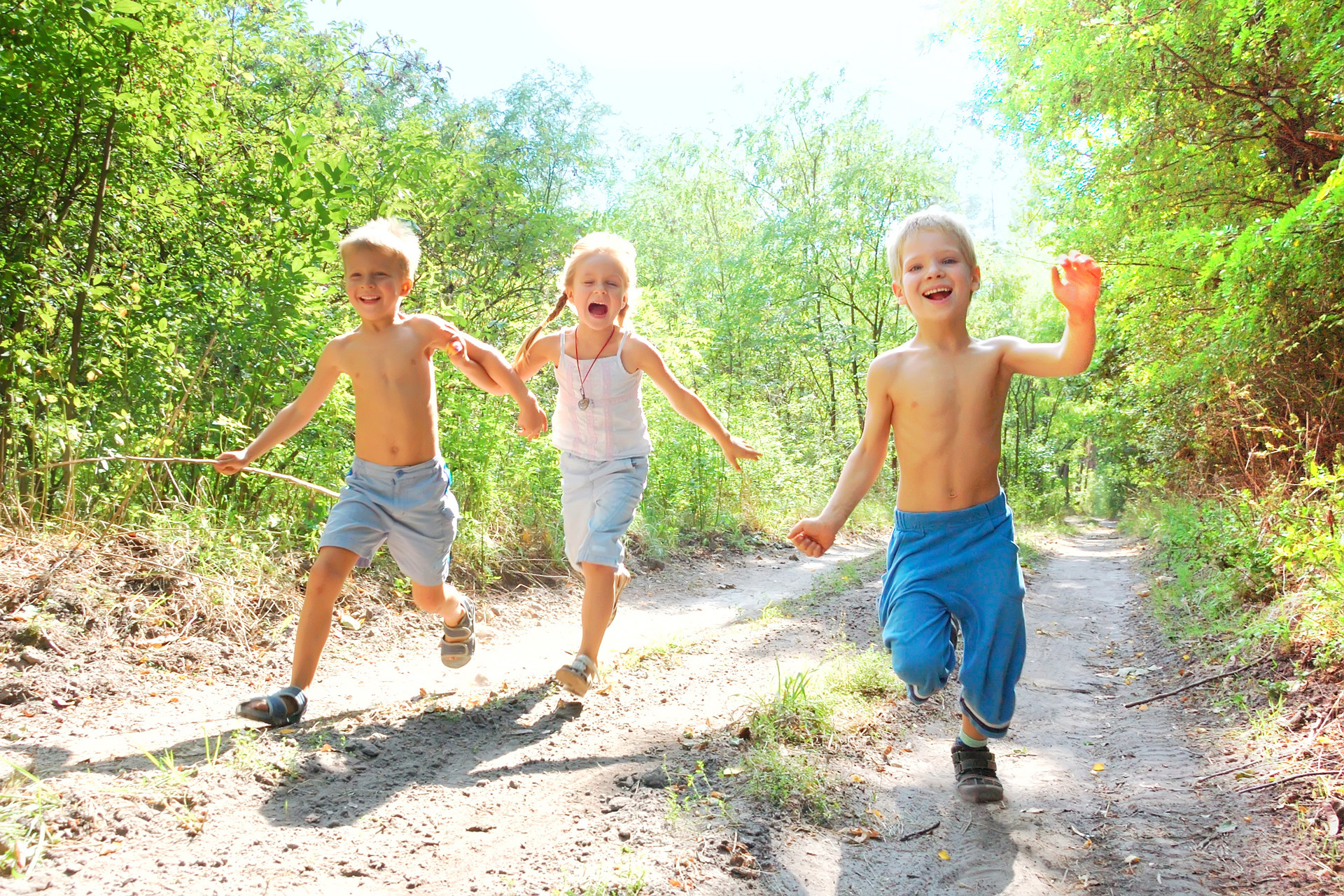 group of 5-6 year old happy kids running in the woods