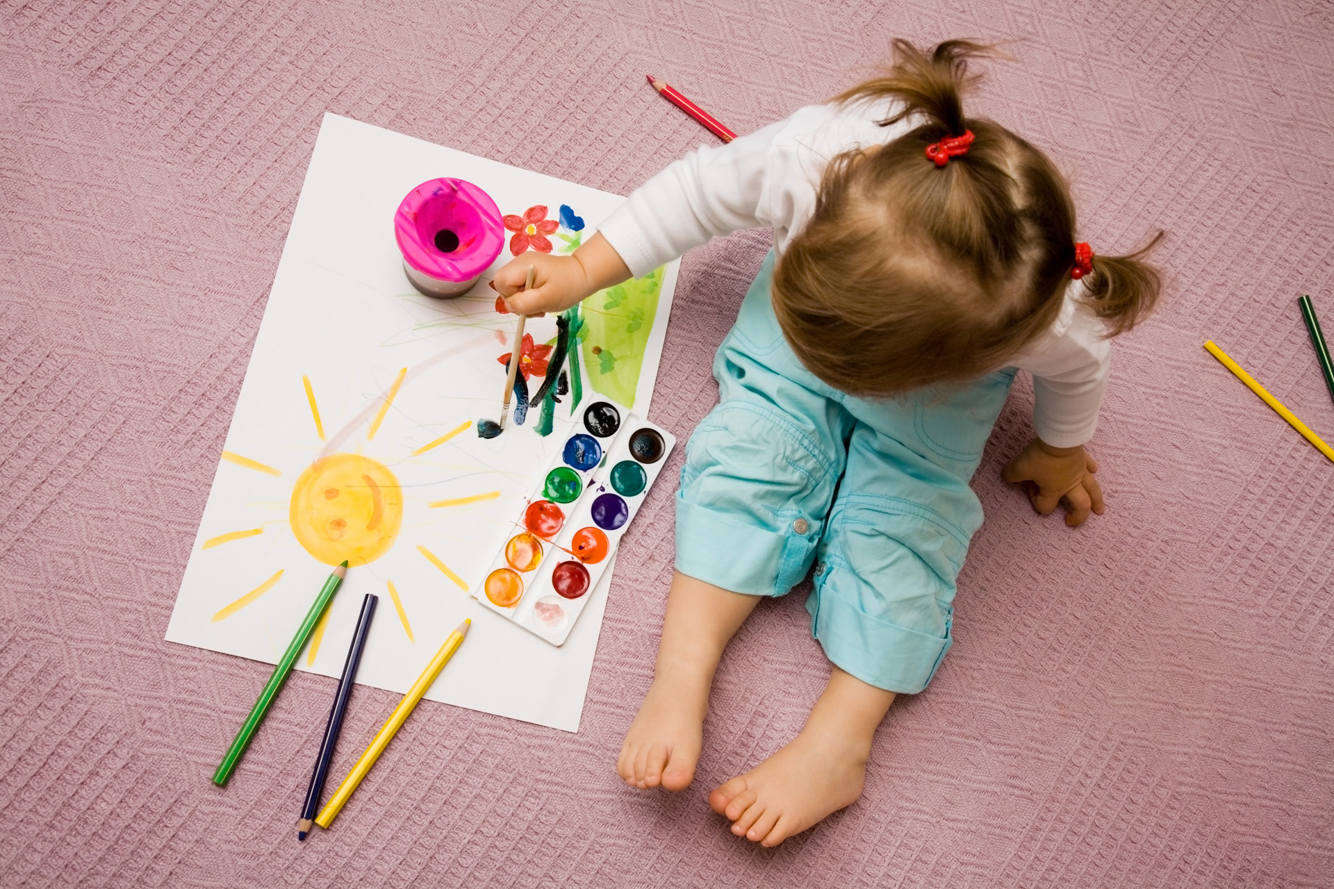 The small beautiful girl paints on a paper