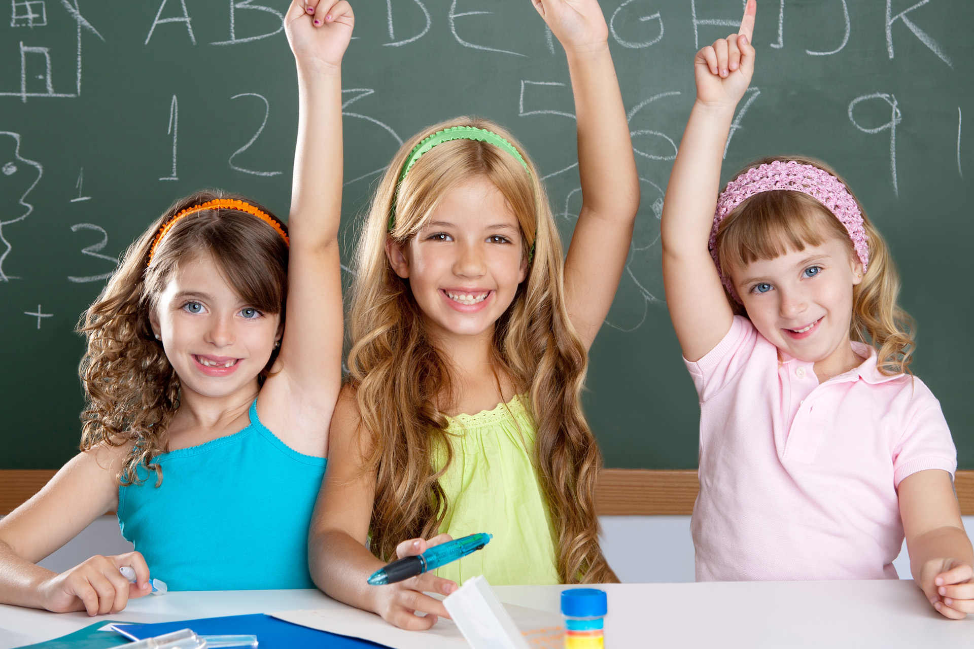 clever kids student group at school classroom raising hand as smart children